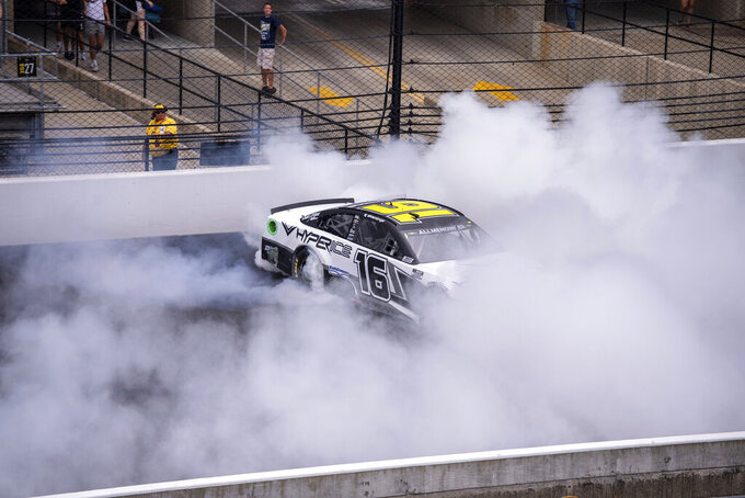 AJ Allmendinger (16) does a burnout at the finish line after winning a NASCAR Cup Series auto race at Indianapolis Motor Speedway, Sunday, Aug. 15, 2021, in Indianapolis. (AP Photo/Doug McSchooler)