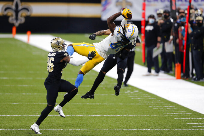 Los Angeles Chargers wide receiver Mike Williams (81) pulls in a pass between New Orleans Saints cornerback P.J. Williams (26) and cornerback Marshon Lattimore (23) in the second half of an NFL football game in New Orleans, Monday, Oct. 12, 2020. The Saints won in overtime 30-27. (AP Photo/Brett Duke)