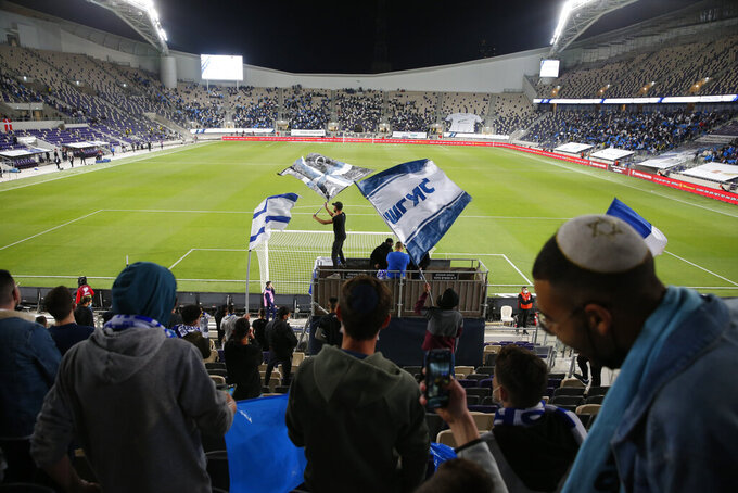 Israeli fans cheer before the World Cup 2022 group F qualifying soccer match between Israel and Denmark in Tel Aviv, Israel, Thursday, March 25, 2021. (AP Photo/Ariel Schalit)