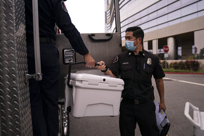 Torrance fire Capt. John Kubota, right, hands a cooler containing the Pfizer COVID-19 vaccine to Alessandro Demuro as they prepare to inoculate two sisters who have muscular dystrophy, at their home, Wednesday, May 12, 2021, in Torrance, Calif. Teamed up with the Torrance Fire Department, Torrance Memorial Medical Center started inoculating people at home in March, identifying people through a city hotline, county health department, senior centers and doctor's offices, said Mei Tsai, the pharmacist who coordinates the program. (AP Photo/Jae C. Hong)