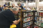 A collector looks through vintage beer cans on display Thursday, Aug. 29, 2019, in Albuquerque, N.M., at the 49th annual gathering of members of the Brewery Collectibles Club of America. Collectors from around the world began Thursday buying, trading and selling containers of brews at the annual four-day event billed the