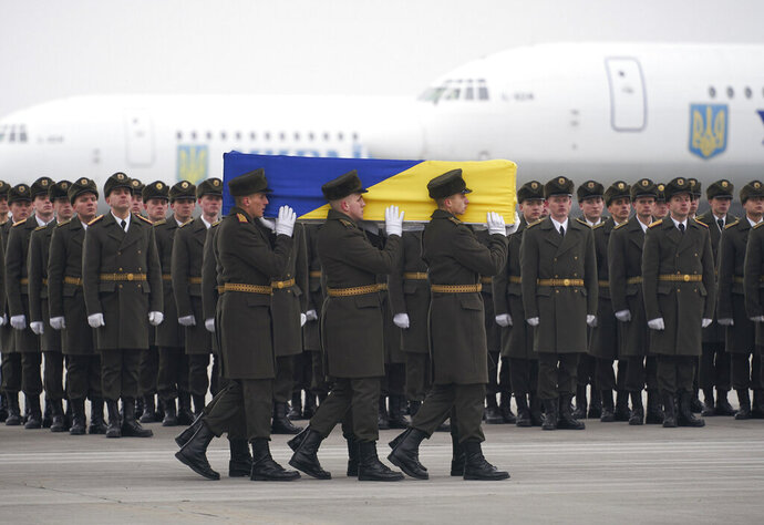 In this photo provided by the Ukrainian Presidential Press Office, honor guards carry a coffin of the one of the eleven Ukrainian victims of the Ukrainian 737-800 plane that crashed on the outskirts of Tehran, during a memorial ceremony at Borispil international airport outside Kyiv, Ukraine, Sunday, Jan. 19, 2020. An Ukrainian passenger jet carrying 176 people has crashed just minutes after taking off from the Iranian capital's main airport on Jan. 8, 2020. (Ukrainian Presidential Press Office via AP)