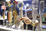 A bartender pours a beer while wearing a mask and face shield amid the coronavirus pandemic at Slater's 50/50 Wednesday, July 1, 2020, in Santa Clarita, Calif. California Gov. Gavin Newsom has ordered a three-week closure of bars, indoor dining and indoor operations of several other types of businesses in various counties, including Los Angeles, as the state deals with increasing coronavirus cases and hospitalizations. (AP Photo/Marcio Jose Sanchez)