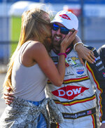 Whitney Dillon, left, kisses her husband, NASCAR Cup Series driver Austin Dillon (3) after he captured the pole in qualifying for a NASCAR Cup Series auto race at Talladega Superspeedway, Saturday, April 27, 2019, in Talladega, Ala. (AP Photo/Julie Bennett)