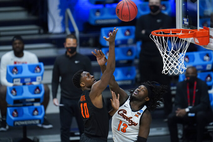 Oregon State forward Warith Alatishe (10) shoots on Oklahoma State forward Matthew-Alexander Moncrieffe (12) during the second half of a men's college basketball game in the second round of the NCAA tournament at Hinkle Fieldhouse in Indianapolis, Sunday, March 21, 2021. (AP Photo/Paul Sancya)