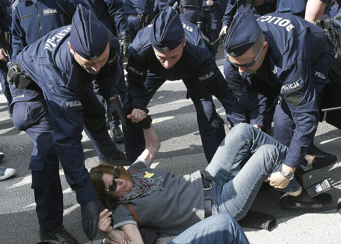 Police remove people who were blocking the march of European Union critics as Poland and other central European nations marked 15 years of EU membership, in Warsaw, Poland, Wednesday, May 1, 2019.(AP Photo/Czarek Sokolowski)