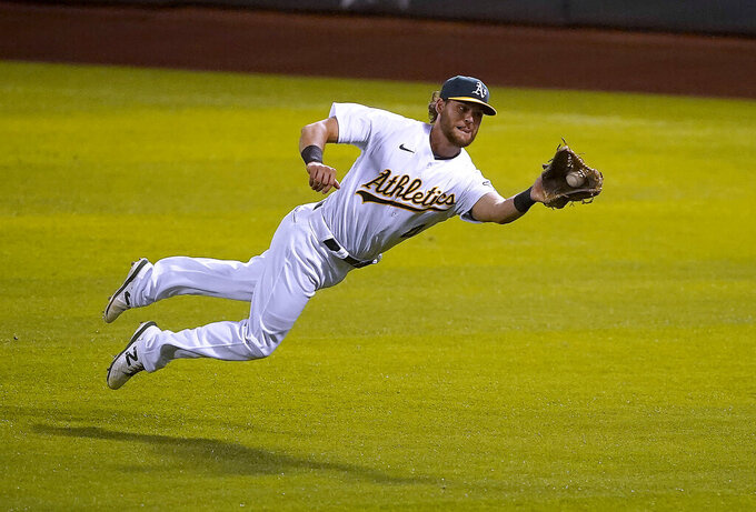 Oakland Athletics right fielder Chad Pinder makes a diving catch on a hit by Houston Astros' Jose Altuve during the fifth inning of an opening day baseball game in Oakland, Calif., Thursday, April 1, 2021. (AP Photo/Tony Avelar)