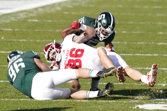 Indiana tight end Peyton Hendershot (86) is tackled by Michigan State defensive end Jacub Panasiuk (96) and cornerback Angelo Grose (15) during the second half of an NCAA college football game, Saturday, Nov. 14, 2020, in East Lansing, Mich. (AP Photo/Carlos Osorio)
