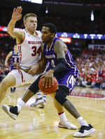 Northwestern's Vic Law (4) drives against Wisconsin's Brad Davison (34) during the first half of an NCAA college basketball game Saturday, Jan. 26, 2019, in Madison, Wis. (AP Photo/Andy Manis)