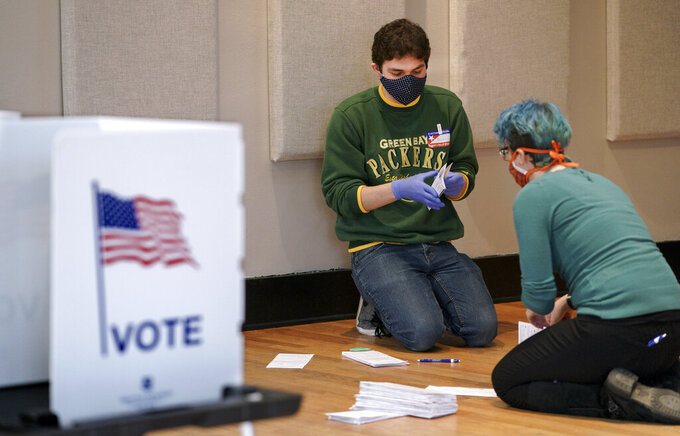 Benjamin Olneck-Brown, left, and Laura Muller organize absentee ballots at the Wil-Mar Neighborhood Center Tuesday,  April 7, 2020 in Madison, Wis.  Voters across the state are ignoring a stay-at-home order in the midst of a pandemic to participate in the state's presidential primary election. (Steve Apps/Wisconsin State Journal via AP)