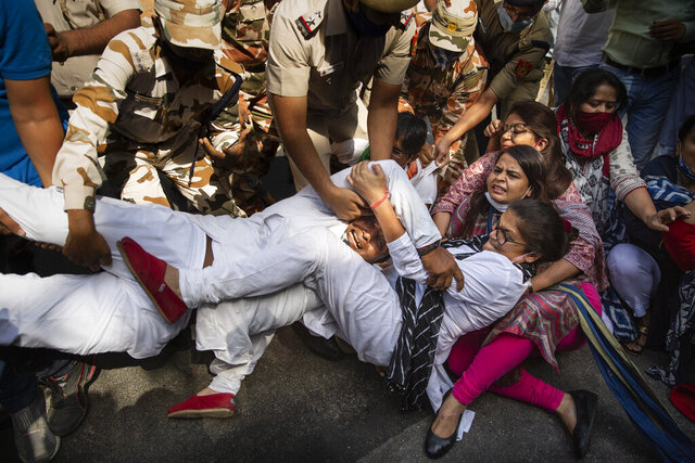 India's opposition Congress party supporters protesting against gang rape and killing of a woman in Uttar Pradesh's Hathras district hold onto each other as Indian policemen try to detain them in New Delhi, India, Wednesday, Sept. 30, 2020. The gang rape and killing of the woman from the lowest rung of India's caste system  has sparked outrage across the country with several politicians and activists demanding justice and protesters rallying on the streets. (AP Photo/Altaf Qadri)