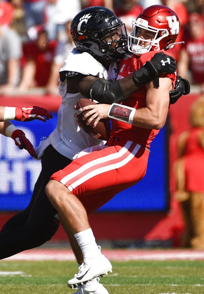 Houston quarterback Logan Holgorsen, right, is sacked by Cincinnati defensive end Myjai Sanders during the first half of an NCAA college football game, Saturday, Oct. 12, 2019, in Houston. (AP Photo/Eric Christian Smith)