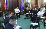 In this Jan. 5, 2020, handout photo provided by the Malacanang Presidential Photographers Division, Philippine President Rodrigo Duterte, center, talks with security officials at the Malacanang presidential palace in Manila, Philippines. Duterte has ordered the military to prepare to deploy its aircraft and ships