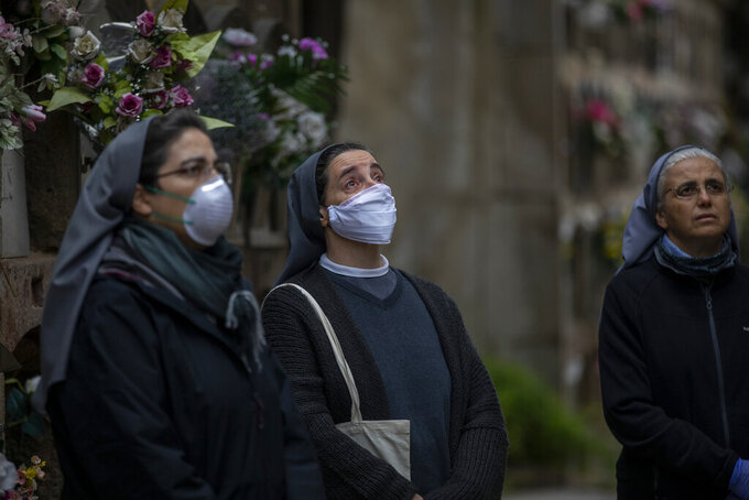 Three nuns look at the coffin of Inmaculada Louzan, a sister of Nazareth who died at age 80 of coronavirus related complications, during her burial at the Poble Nou cemetery in Barcelona, Spain, Saturday, April 18, 2020. (AP Photo/Emilio Morenatti)