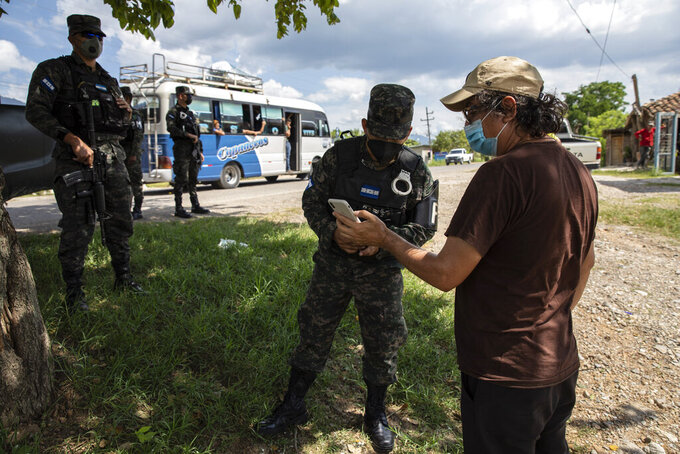 Friar Leopoldo Serrano, right, shows soldiers images he made with his cellphone of a suspicious truck seen near the entrance of his mission, in Mission San Francisco de Asis, Honduras, Friday, June 25, 2021. Serrano's message is not widely popular. He has sought protection for his mission, which is routinely observed by men passing by in oversized SUVs with tinted windows. (AP Photo/Rodrigo Abd)