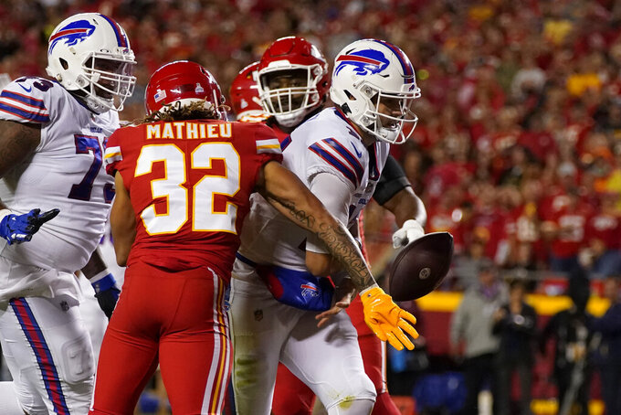 Buffalo Bills quarterback Josh Allen, right, scores a touchdown as the ball is knocked away by Kansas City Chiefs safety Tyrann Mathieu (32) during the first half of an NFL football game Sunday, Oct. 10, 2021, in Kansas City, Mo. (AP Photo/Charlie Riedel)
