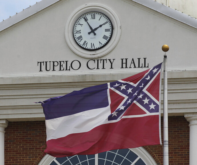 The State Flag of Mississippi waves one last time in the breeze over the City Hall of Tupelo Mississippi Monday, June 29, 2020, just moments before city officials lowered the flag for the last time and presented it to the city's museum. Mississippi is retiring the last state flag in the U.S. that includes the Confederate battle emblem. (Thomas Wells/Northeast Mississippi Daily Journal, Via AP)
