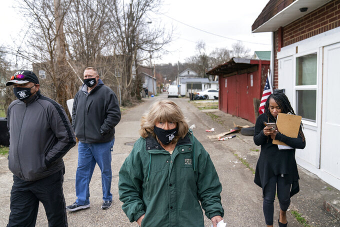 "Sue Howland, center, walks down a street to check on someone who overdosed days before with fellow members of the the Quick Response Team, from left, pastor Virgil Johnson, Sgt. Greg Moore and Larrecsa Cox, Monday, March 15, 2021, in Huntington, W.Va. Howland, the 62-year-old peer recovery coach, nearly drank herself to death. She's been sober now for 10 years. ""We're going to love them until they learn to love themselves,"" said Howland of the people she tries to help. ""We're going to love them back to life."" (AP Photo/David Goldman)"