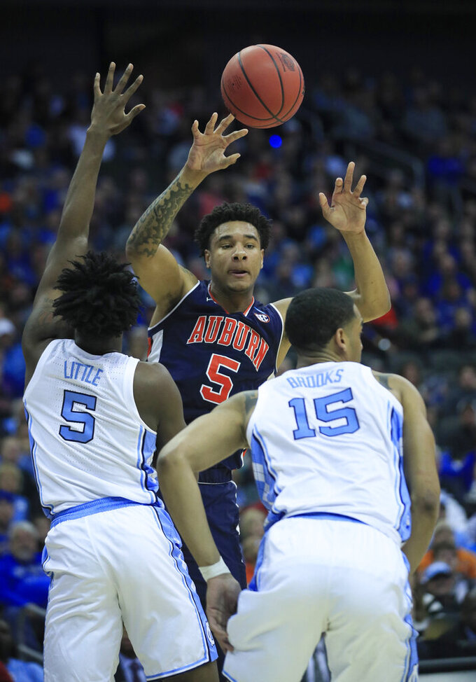 Auburn's Chuma Okeke (5) passes over North Carolina's Nassir Little (5) and Garrison Brooks during the first half of a men's NCAA tournament college basketball Midwest Regional semifinal game Friday, March 29, 2019, in Kansas City, Mo. (AP Photo/Orlin Wagner)