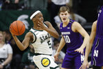 Michigan State guard Cassius Winston (5) passes as Northwestern forward Miller Kopp (10) defends during the first half of an NCAA college basketball game, Wednesday, Jan. 29, 2020, in East Lansing, Mich. (AP Photo/Carlos Osorio)