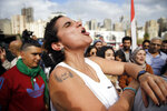 A protester with a tattoo on her arm that reads in Arabic
