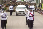 In this image from a video, a band leads funeral procession for the late Tongan Prime Minister 'Akilisi Pohiva in Nuku'alofa, Tonga Thursday, Sept. 19, 2019. Hundreds of mourners packed a church service on Thursday and children stood vigil on downtown streets as Tonga took a national holiday to bid farewell to Pohiva at a state funeral. (TVNZ via AP)
