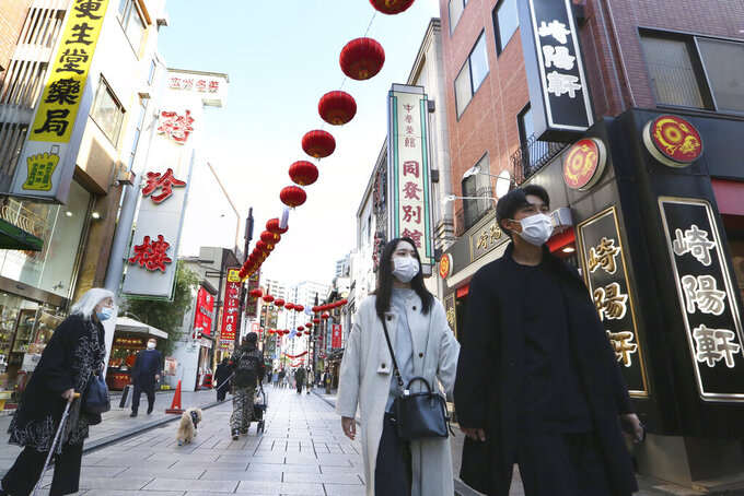 People wearing face masks to protect against the spread of the coronavirus walk through China Town in Yokohama, Kanagawa prefecture, near Tokyo, Tuesday, Dec. 1, 2020. (AP Photo/Koji Sasahara)