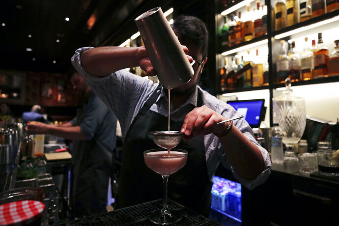 In this Dec. 10, 2019, photo mixologist Julian Bernal crafts a cocktail at Wink & Nod, basement-dwelling, speakeasy-like bar, in Boston. Americans are consuming more alcohol per capita now than in the time leading up to Prohibition, when alcohol opponents successfully made the case that excessive drinking was ruining family life. (AP Photo/Charles Krupa)