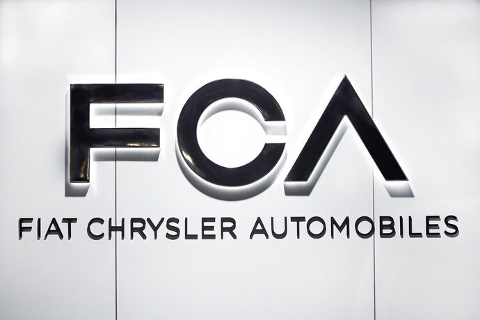 FILE - In this Monday, Jan. 14, 2019 file photo, Fiat Chrysler Automobiles FCA logo is shown at the North American International Auto Show in Detroit. Fiat Chrysler overcame coronavirus-related factory shutdowns to post losses that were not as bad as feared, and the company predicted improvement for the remainder of 2020.  (AP Photo/Paul Sancya, file)