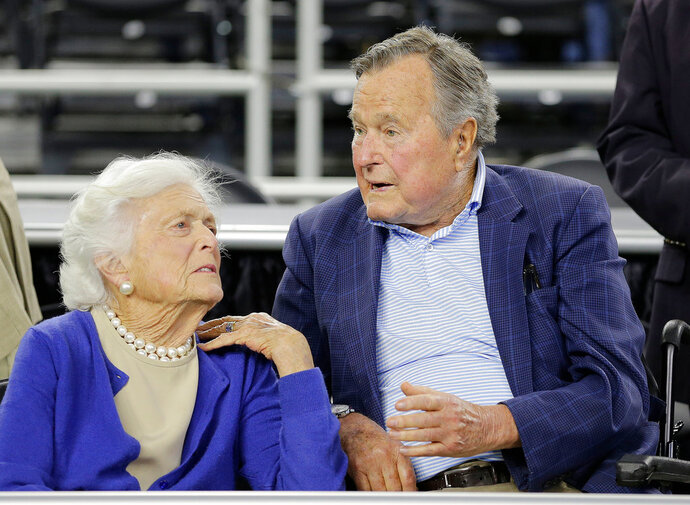 FILE - In this March 29, 2015, file photo, former President George H.W. Bush and his wife Barbara Bush, left, speak before a college basketball regional final game between Gonzaga and Duke, in the NCAA basketball tournament in Houston. A family spokesman said Sunday, April 15, 2018, that the former first lady Barbara Bush is in