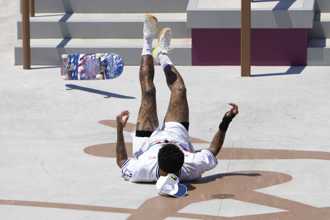 Nyjah Huston of the United States tumbles during the men's street skateboarding finals at the 2020 Summer Olympics, Sunday, July 25, 2021, in Tokyo, Japan. (AP Photo/Jae C. Hong)