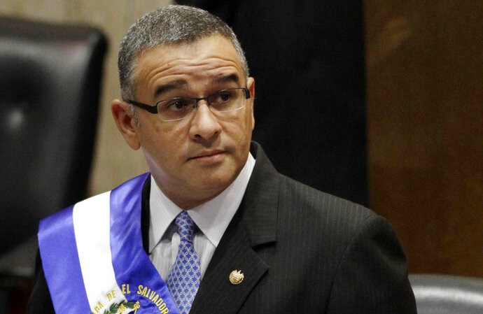 FILE - In this June 1, 2012 file photo, El Salvador's President Mauricio Funes stands in the National Assembly before speaking to commemorate the anniversary of his third year in office in San Salvador, El Salvador. Prosecutors in El Salvador are seeking on Friday, Sept. 14, 2018, the extradition of former President Mauricio Funes and three family members on corruption charges. Funes, the relatives and ex-officials are accused in connection the alleged embezzlement of $351 million in public funds. (AP Photo/Luis Romero, File)