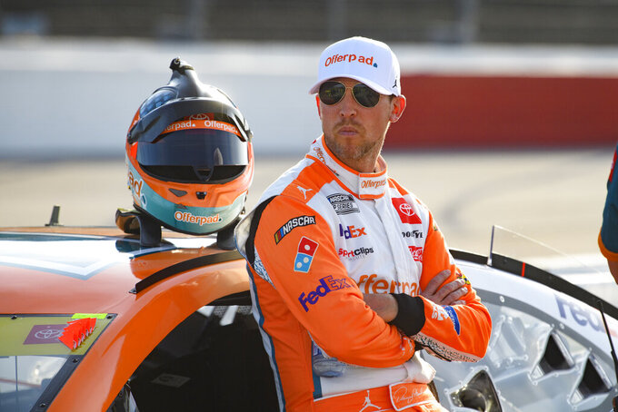Denny Hamlin stands by his car before a NASCAR Cup Series auto race Sunday, Sept. 5, 2021, in Darlington, S.C. (AP Photo/John Amis)