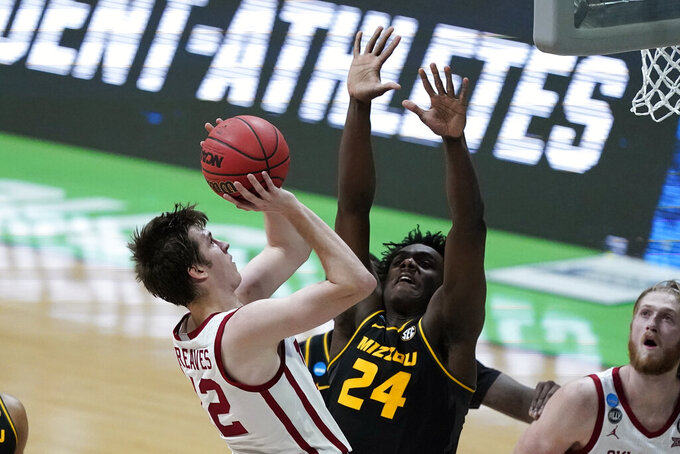 Oklahoma guard Austin Reaves, left, shoots over Missouri forward Kobe Brown (24) during the first half of a first-round game in the NCAA men's college basketball tournament at Lucas Oil Stadium, Saturday, March 20, 2021, in Indianapolis. (AP Photo/Darron Cummings)