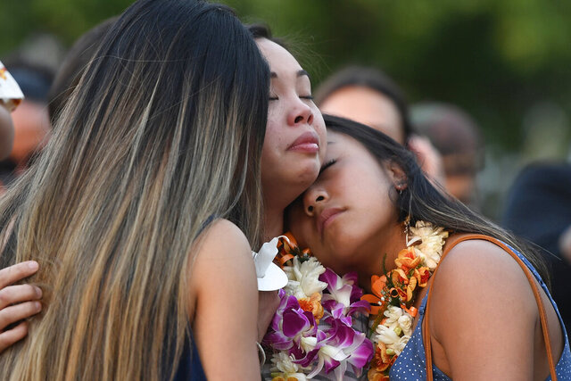 In this Tuesday, Jan. 21, 2020, photo, Teiya Enriquez Sandoval, center, and her sister Jazzy Enriquez, right, the daughters of Honolulu Police Officer Tiffany Enriquez, hug family friend Tristel Tynanaes during a candlelight vigil in remembrance of Tiffany Enriquez in Honolulu. A handyman's landlord had recently started an eviction process before he stabbed a woman Sunday and fatally shot two Honolulu officers, including Enriquez. (Bruce Asato/Honolulu Star-Advertiser via AP)