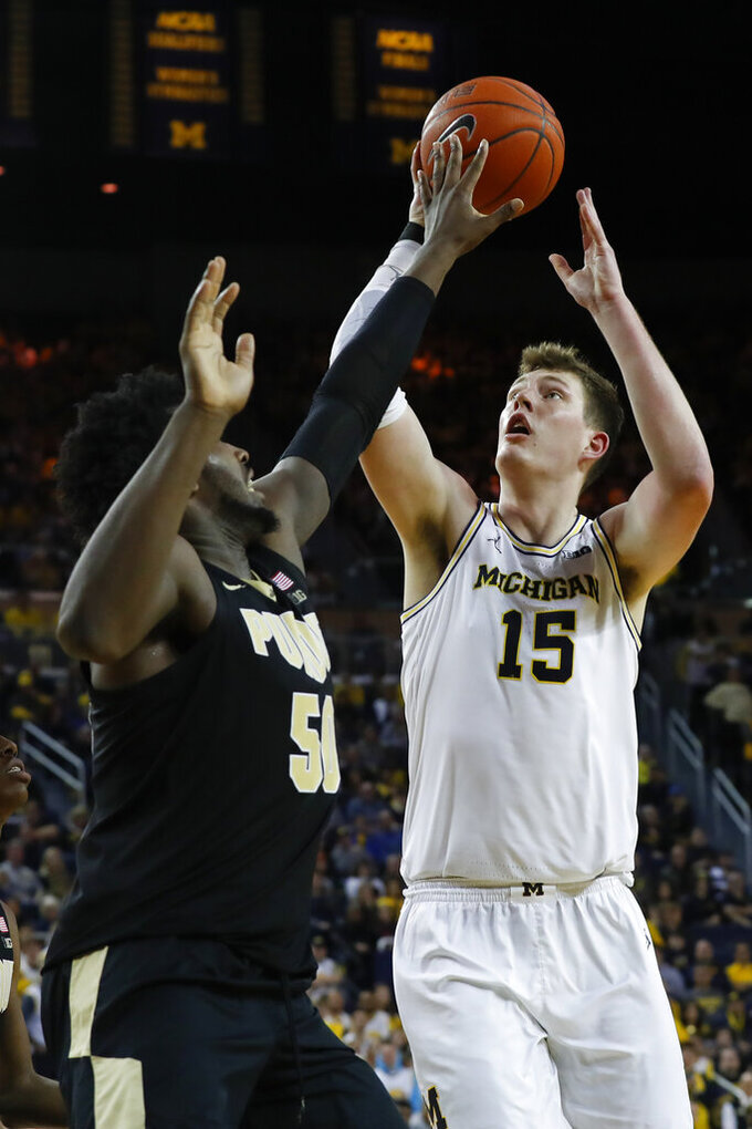 Michigan center Jon Teske (15) shoots next to Purdue forward Trevion Williams (50) during the second half of an NCAA college basketball game in Ann Arbor, Mich., Thursday, Jan. 9, 2020. (AP Photo/Paul Sancya)