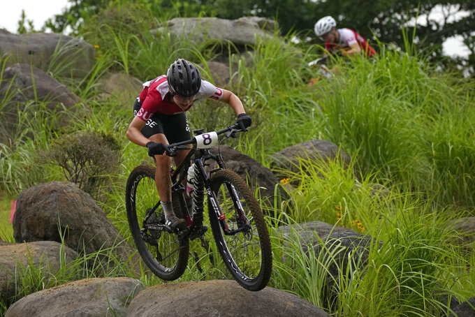 Sina Frei of Switzerland and Linda Indergand of Switzerland, top right, compete during the women's cross-country mountain bike competition at the 2020 Summer Olympics, Tuesday, July 27, 2021, in Izu, Japan. (AP Photo/Christophe Ena)