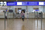 A girl wearing a mask skips rope at Incheon International Airport in Incheon, South Korea, Monday, Jan. 27, 2020. China on Monday expanded sweeping efforts to contain a viral disease by extending the Lunar New Year holiday to keep the public at home and avoid spreading infection. (AP Photo/Ahn Young-joon)