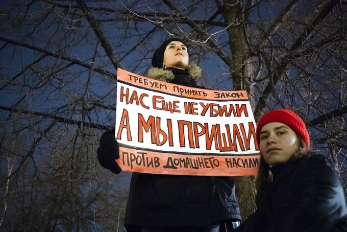 """FILE - In this Nov. 25, 2019, file photo, a woman holds a banner reading, """"We demand the adoption of a law against domestic violence. We have not been killed yet, but we're close,"""" as she attends a rally in Moscow, Russia. Few reliable official statistics are kept on violence against women in Russia, but it is clearly a national problem. Police routinely turn a blind eye to domestic abuse, and restraining orders don't exist, leaving victims without a key protection. (AP Photo/Pavel Golovkin, File)"""
