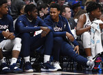 Connecticut starter Jalen Adams, who is out injured, right, talks with teammate Mamadou Diarra, left, during the first half of an NCAA college basketball game against Houston, Thursday, Feb. 14, 2019, in Hartford, Conn. (AP Photo/Jessica Hill)