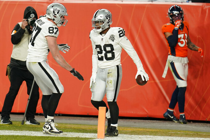 Las Vegas Raiders tight end Foster Moreau (87) and running back Josh Jacobs (28) celebrate after Jacobs scored a touchdown against the Denver Broncos during the second half of an NFL football game, Sunday, Jan. 3, 2021, in Denver. (AP Photo/Jack Dempsey)