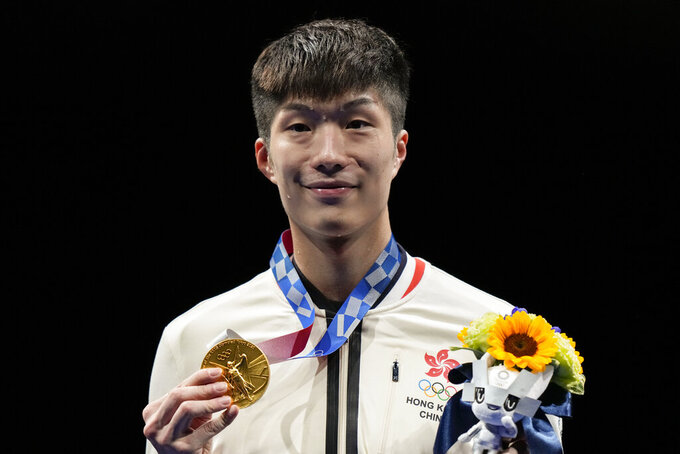 Ka Long Cheung of Hong Kong holds the gold medal during the awarding ceremony of the men's individual Foil competition at the 2020 Summer Olympics, Monday, July 26, 2021, in Chiba, Japan. (AP Photo/Andrew Medichini)