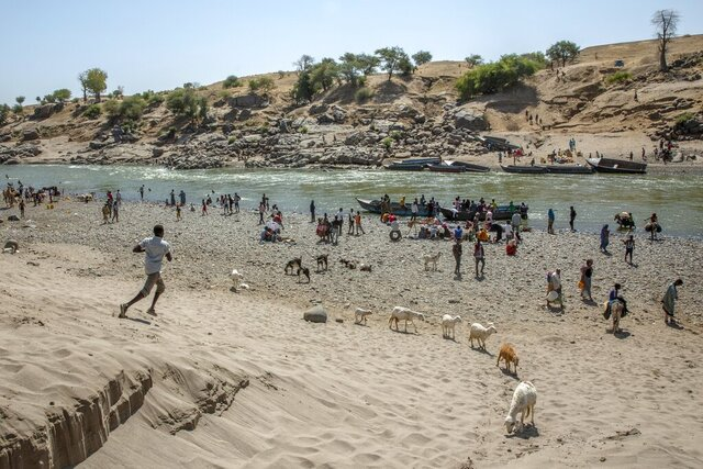 Tigray refugees who fled the conflict in the Ethiopia's Tigray arrive on the banks of the Tekeze River on the Sudan-Ethiopia border, in Hamdayet, eastern Sudan, Saturday, Nov. 21, 2020. The U.N. refugee agency says Ethiopia's growing conflict has resulted in thousands fleeing from the Tigray region into Sudan as fighting spilled beyond Ethiopia's borders and threatened to inflame the Horn of Africa region. (AP Photo/Nariman El-Mofty)