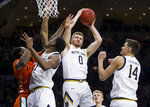 Notre Dame's Rex Pflueger (0) grabs a rebound during the first half of an NCAA college basketball game against Miami on Sunday, Feb. 23, 2020, in South Bend, Ind. (AP Photo/Robert Franklin)