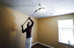 Painter Thaddius Owens paints a bedroom ceiling in a newly built home at 1995 Whitney in Frayser, Tenn. Wednesday, July 17, 2019. (Mark Weber/Daily Memphian via AP)