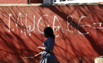 A woman walks past a graffiti sign in Harare, Sept. 6, 2019. As controversy continues around the burial of Mugabe, the capital, Harare, bustles with people coping with the challenges of daily life amid widespread shortages. (AP Photo/Tsvangirayi Mukwazhi, File)