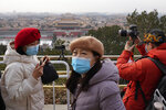 Visitors wear masks as they enjoy the view overlooking the Forbidden City from Jingshan park during a snow day in Beijing Tuesday, Jan. 19, 2021. China is now dealing with coronavirus outbreaks across its frigid northeast, prompting additional lockdowns and travel bans. (AP Photo/Ng Han Guan)