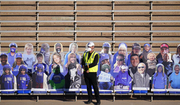 A guard stands in front of fan cutouts in the otherwise empty east stands of Falcon Stadium during the first half of an NCAA college football game between Air Force and Boise State on Saturday Oct. 31, 2020, at Air Force Academy, Colo. (AP Photo/David Zalubowski)