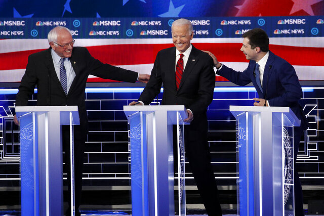 Democratic presidential candidates Sen. Bernie Sanders, I-Vt., left, and former South Bend Mayor Pete Buttigieg, right, reach for former Vice President Joe Biden during a Democratic presidential primary debate Wednesday, Feb. 19, 2020, in Las Vegas, hosted by NBC News and MSNBC. (AP Photo/John Locher)