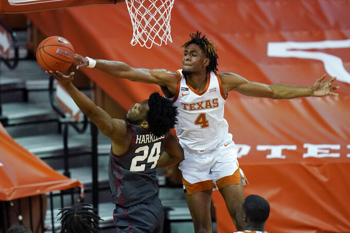 Oklahoma guard Elijah Harkless (24) is blocked by Texas forward Greg Brown (4) during the first half of an NCAA college basketball game Tuesday, Jan. 26, 2021, in Austin, Texas. (AP Photo/Eric Gay)
